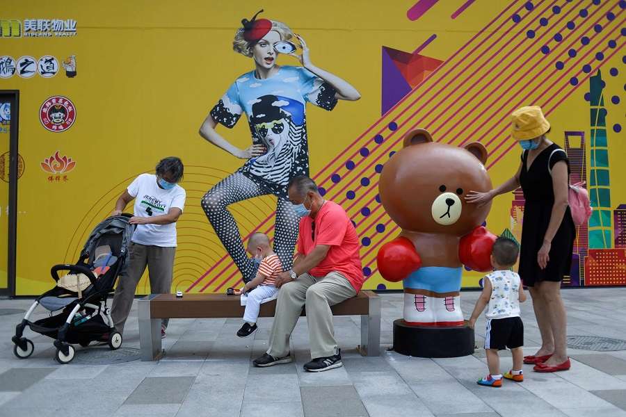 A group of people with young children relax along a pavement in Beijing on 23 July 2020. (Wang Zhao/AFP)
