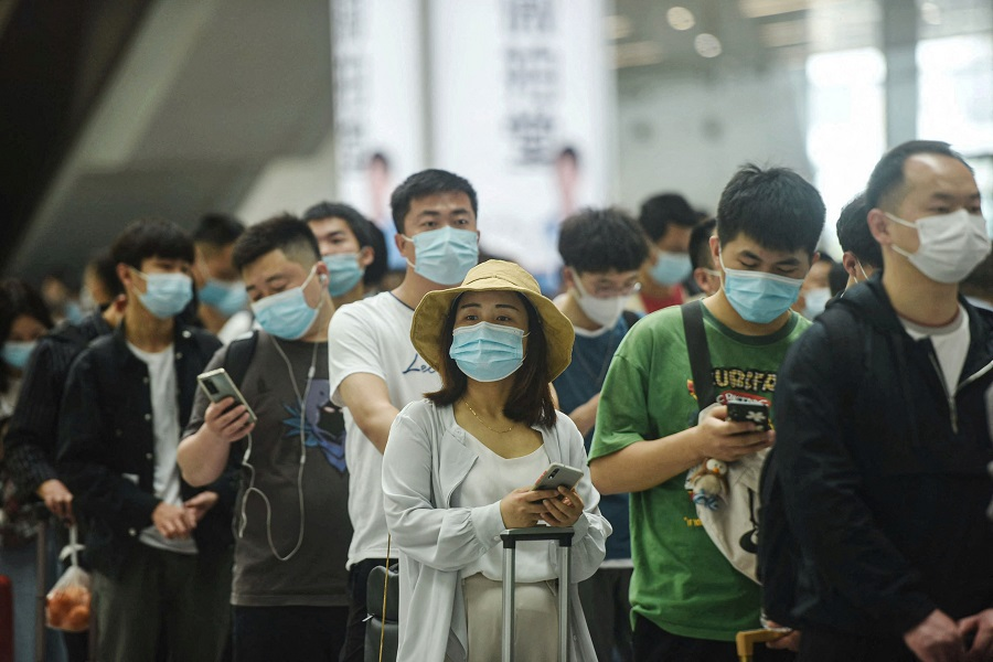 Passengers use their mobile phones as they prepare to board trains at Hangzhou East train station in Hangzhou, Zhejiang province, China, on 30 April 2021. (STR/AFP)