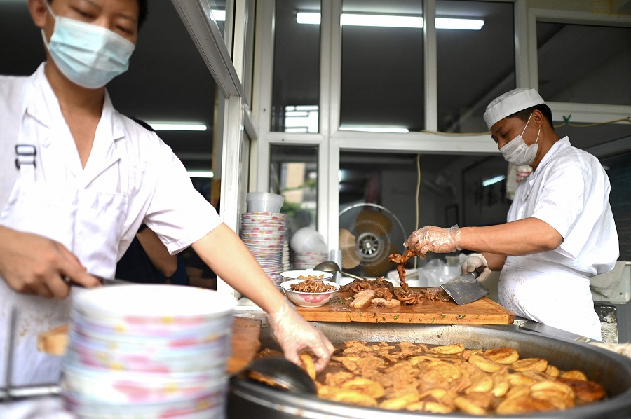 Cooks prepare a traditional Beijing street food, luzhu huoshao, a pork stew with bread, at a restaurant in Beijing, China, on 3 August 2021. (Noel Celis/AFP)