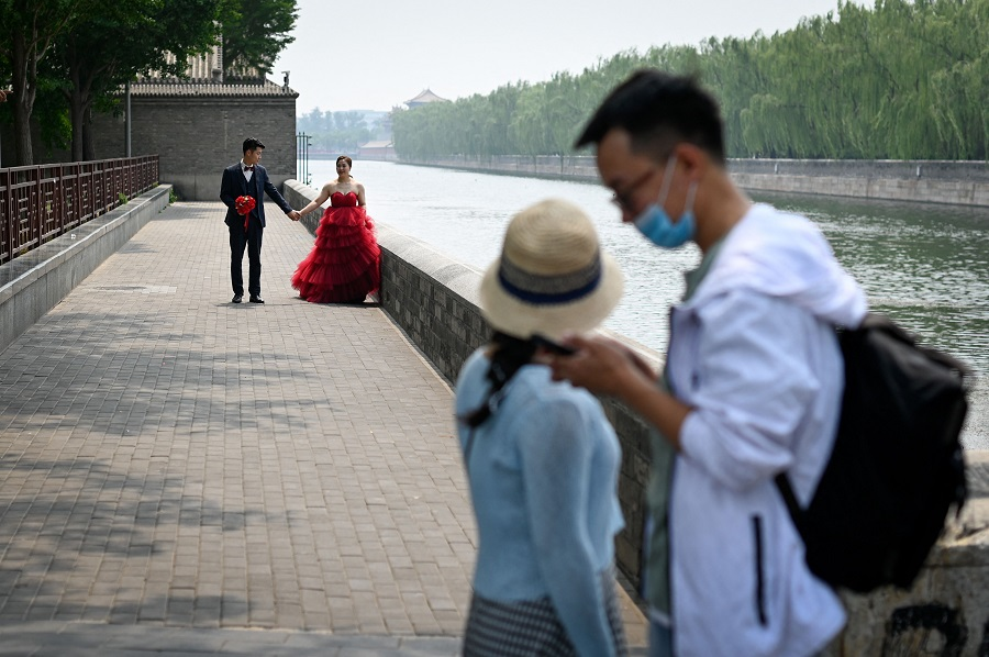 A couple (back) poses for wedding photos near the Forbidden City in Beijing, China, on 20 May 2021. (Wang Zhao/AFP)