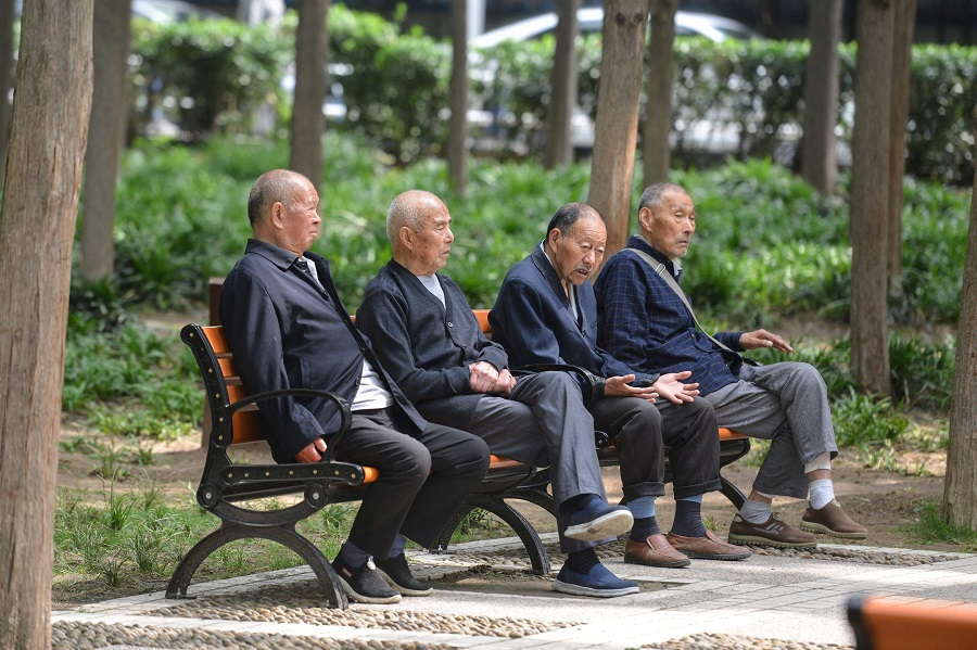 Elderly people rest at a park in Fuyang, Anhui province, China, on 12 May 2021. (STR/AFP)