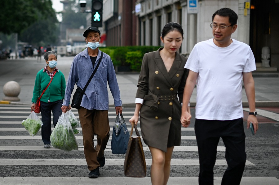 People walk across a street in Beijing, China, on 31 May 2021. (Wang Zhao/AFP)
