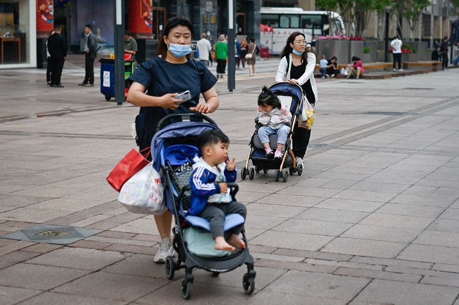 Two women push strollers along a business street in Beijing, China, on 31 May 2021. (Wang Zhao/AFP)