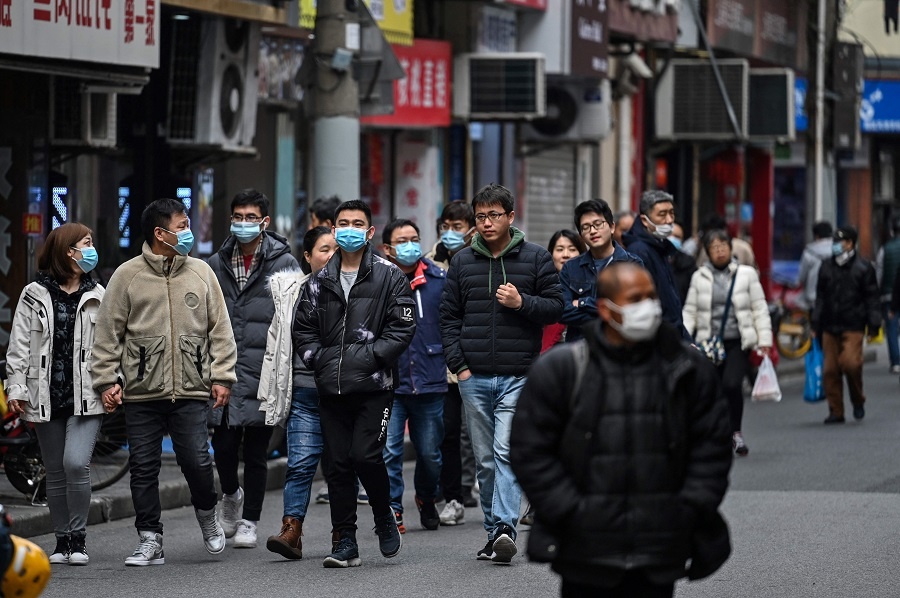 People walk along a street in Shanghai on 5 March 2021. (Hector Retamal/AFP)