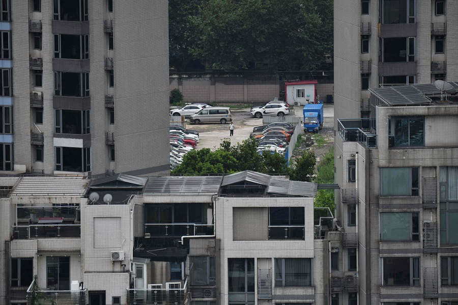 A security guard walks in a car park behind residential buildings in Shanghai, China, on 16 August 2021. (Greg Baker/AFP)