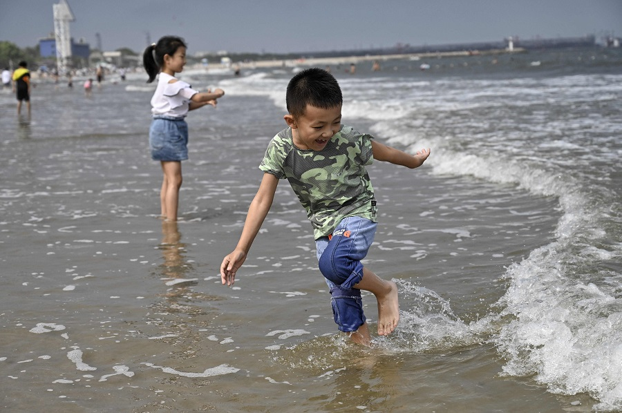 Children play on a beach in Qinhuangdao, Hebei province, China, on 4 July 2021. (Jade Gao/AFP)