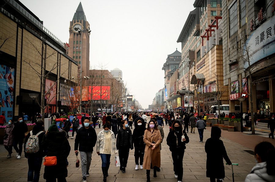 People walk along Wangfujing shopping street in Beijing, China, on 14 February 2021. (Noel Celis/AFP)