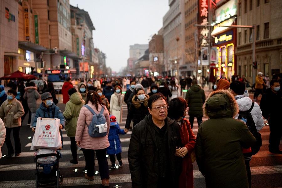 People walk along Wangfujing shopping street in Beijing, China, on 14 February 2021. (Noel Celis/AFP)