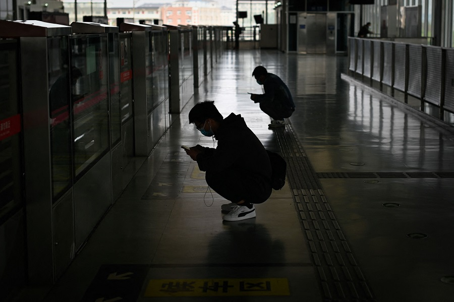 Two men use their mobile phone as they squat waiting for a train at a subway station in Beijing, China, on 26 April 2021. (Wang Zhao/AFP)