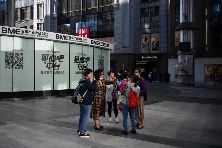 A group of women chat outside a shopping mall in Beijing on 17 September 2020. A Uniqlo logo can be seen in the background. (Greg Baker/AFP)