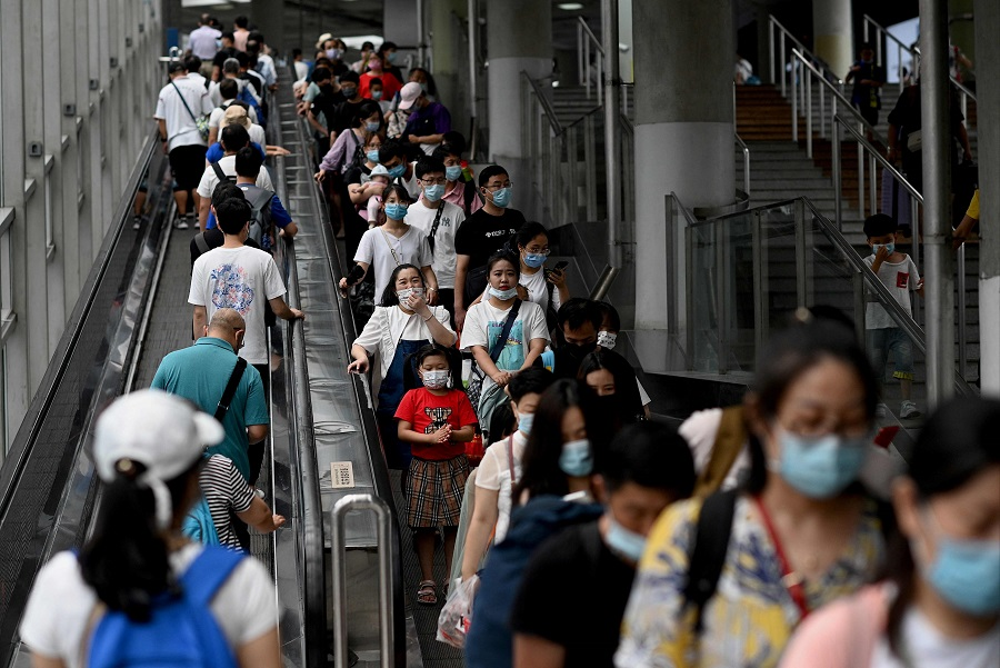 People ride escalators during rush hour at the subway in Beijing, China, on 28 July 2021. (Noel Celis/AFP)