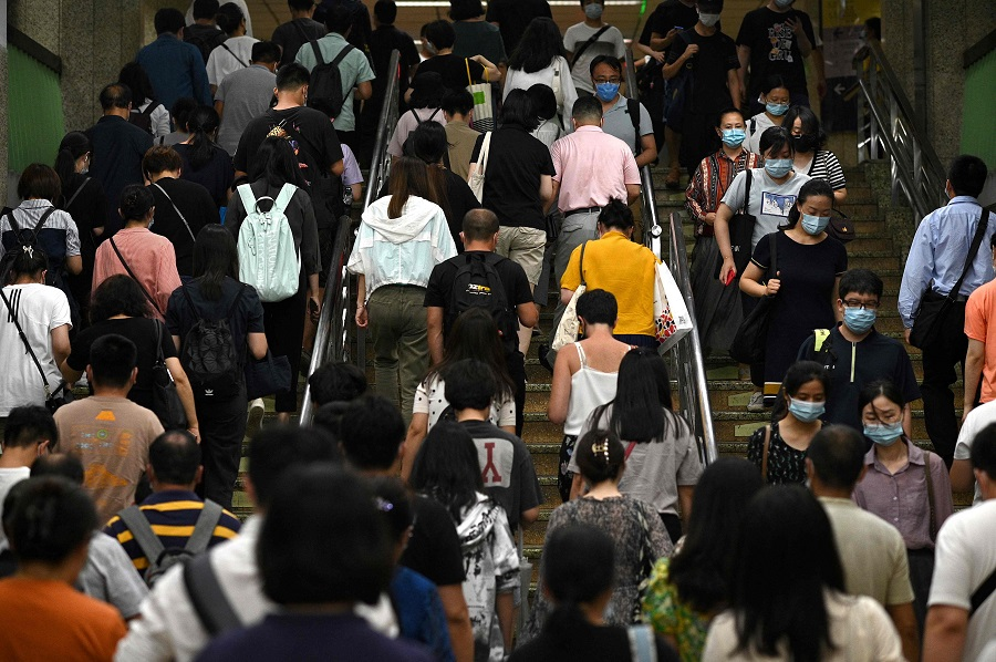 People walk up the stairs during rush hour at a subway in Beijing, China, on 28 July 2021. (Noel Celis/AFP)