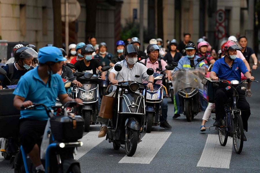 People ride electric scooters during rush hour in Shanghai, China, on 3 September 2021. (Greg Baker/AFP)