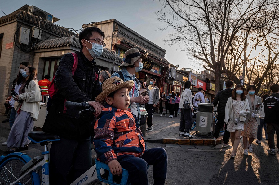 A young boy (centre) is pushed along on a bicycle on a street in Beijing, China, on 4 April 2021. (Nicolas Asfouri/AFP)
