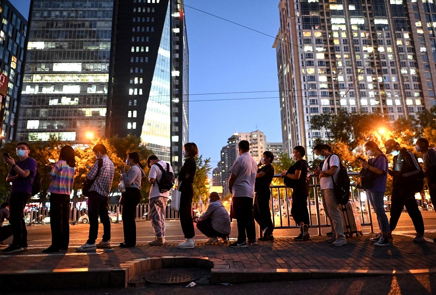 People queue at a bus stop during evening rush hour in Beijing, China, on 27 August 2021. (Noel Celis/AFP)