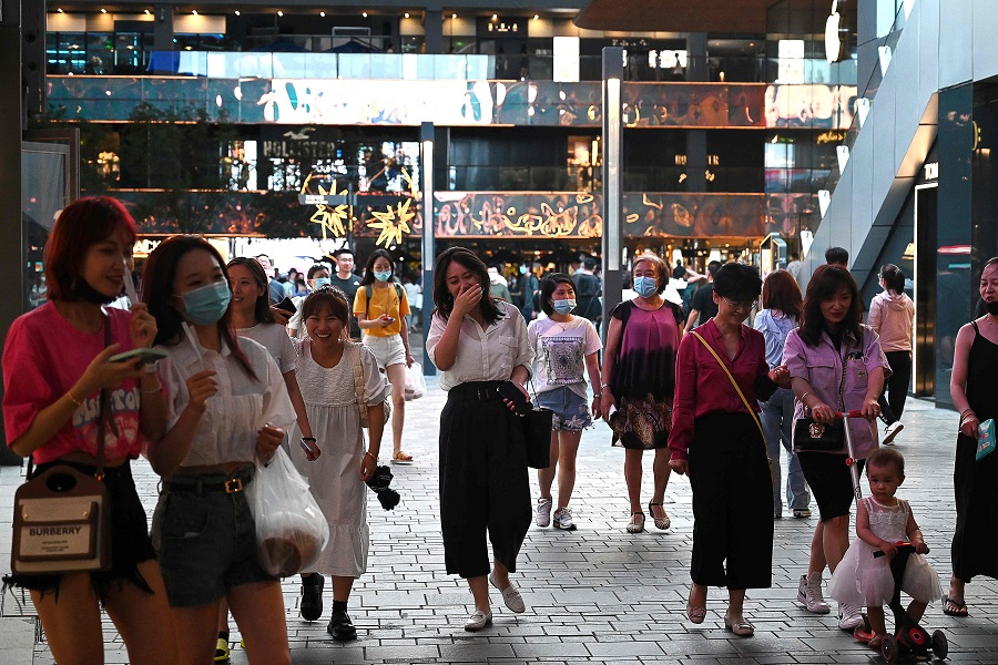 People walk in a shopping mall in Beijing, China on 21 June 2021. (Greg Baker/AFP)