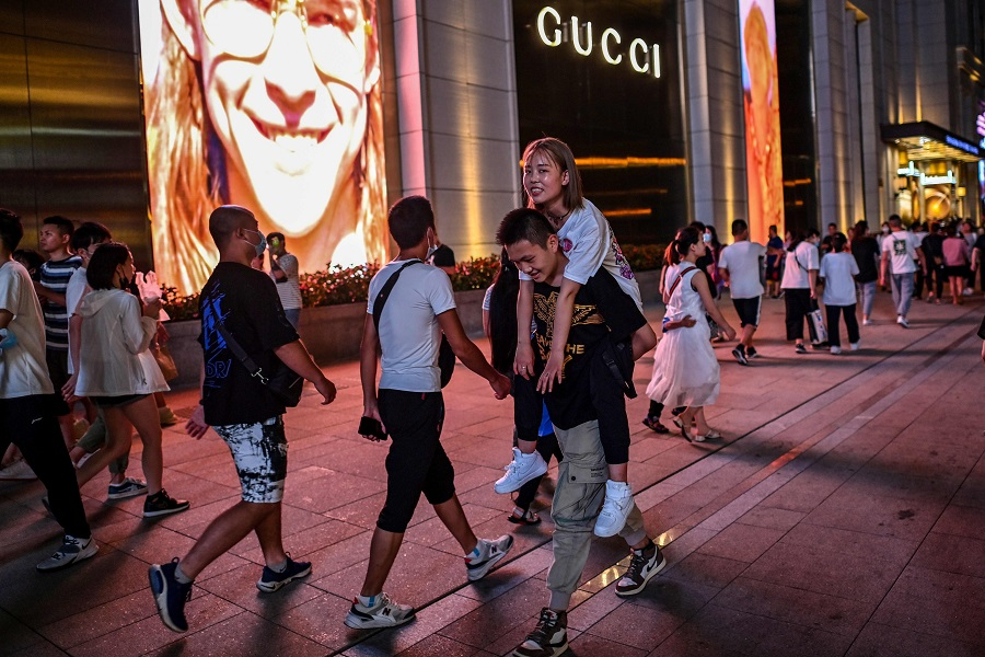 People walk on a street surrounded by shops and malls in Shanghai on 31 July 2020. (Hector Retamal/AFP)