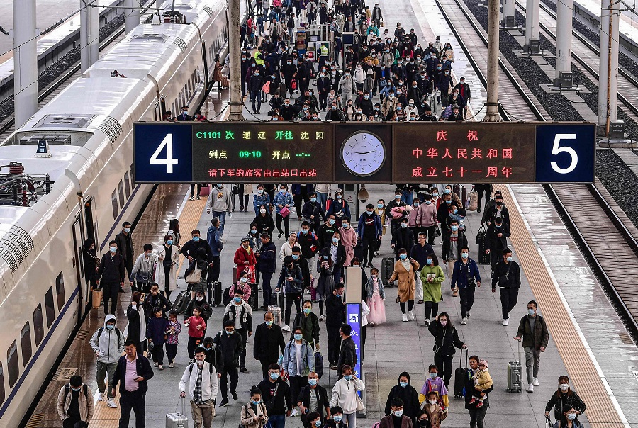 People arrive at Shenyang Railway Station in Liaoning, China, on 7 October 2020. (STR/AFP)