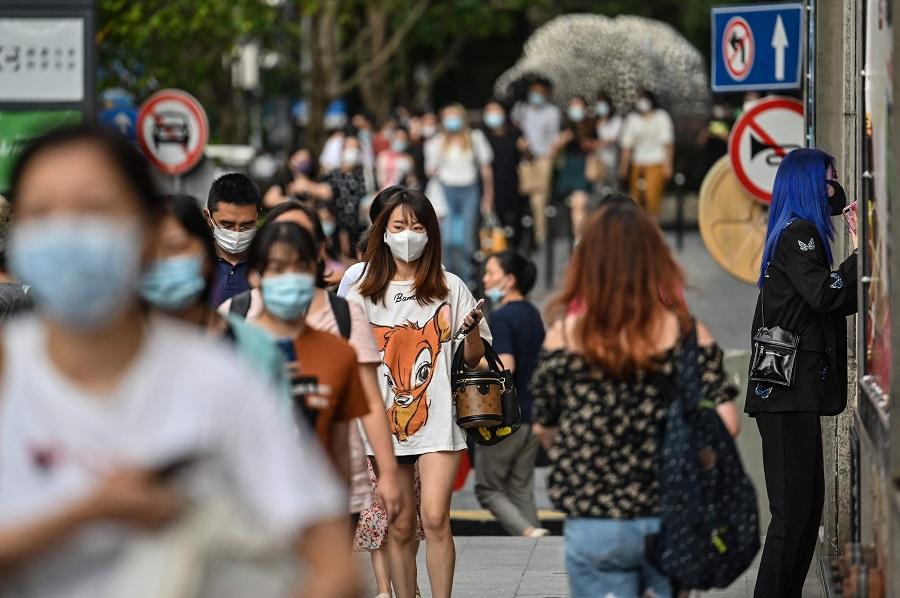 People walk on a street in Shanghai, China, on 5 August 2021. (Hector Retamal/AFP)