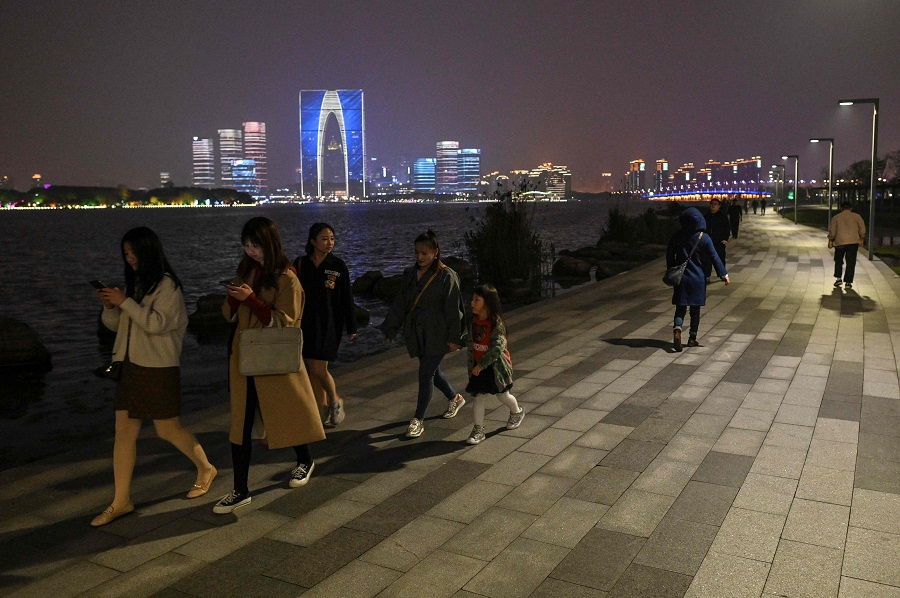 People walk on a promenade next to the Jinji Lake in Suzhou, Jiangsu province, China, on 12 April 2021. (Hector Retamal/AFP)