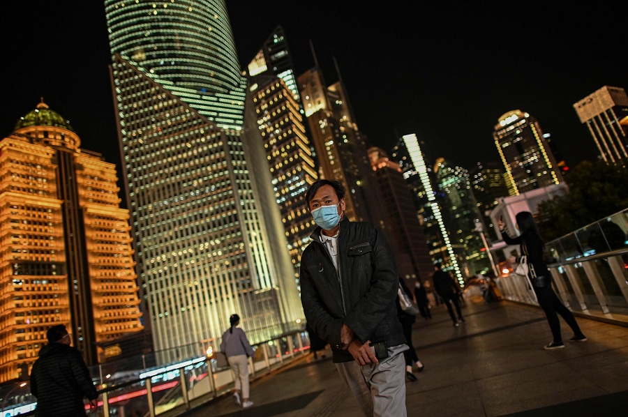 A man wearing a face mask walks over a bridge in the financial district of Lujiazu in Shanghai on 9 November 2020 (Hector Retamal/AFP)