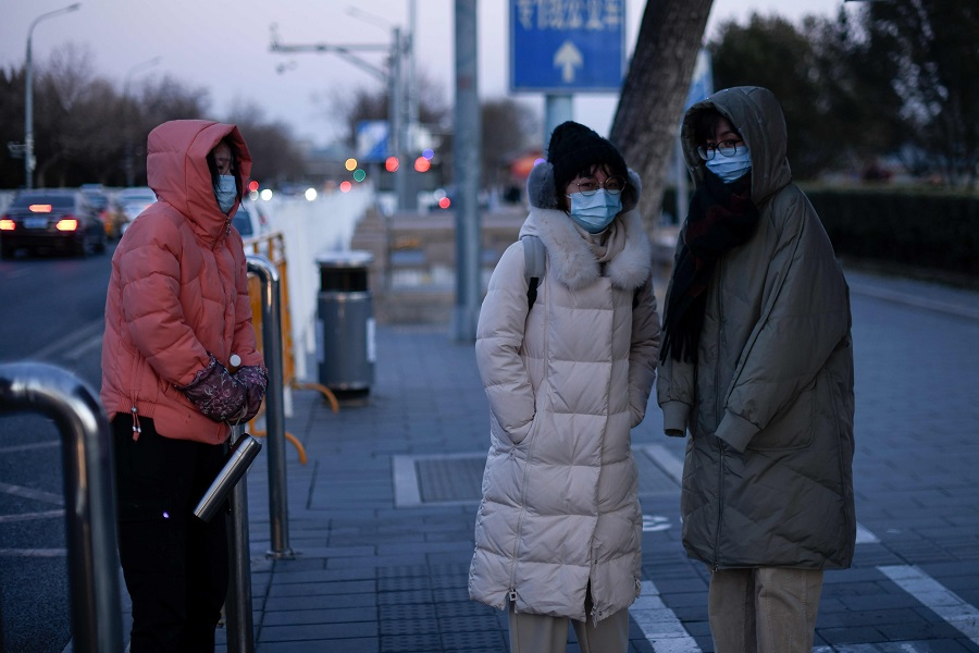 Women wearing face masks stand at a bus station on a cold winter day in Beijing on 29 December 2020. (Wang Zhao/AFP)