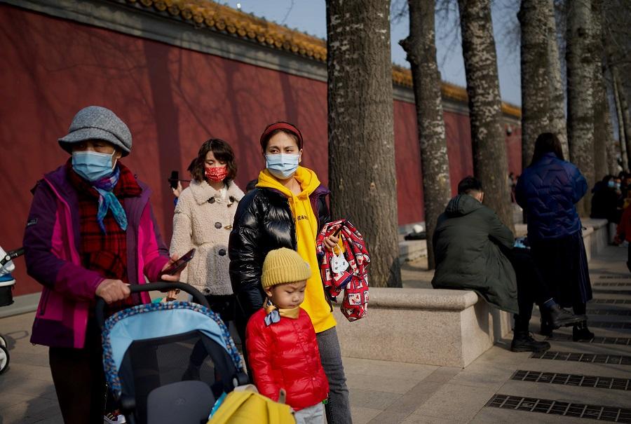 People wearing face masks wait near Tiananmen Gate in Beijing, China, on 12 February 2021. (Noel Celis/AFP)