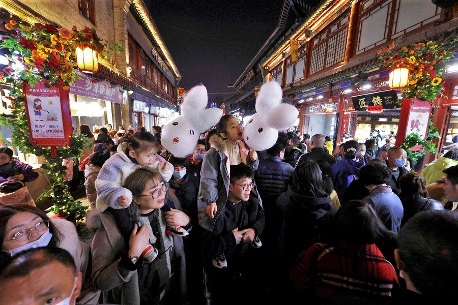 People walk on a commercial street in Taiyuan, Shanxi province, China on 26 February 2021. (STR/AFP)