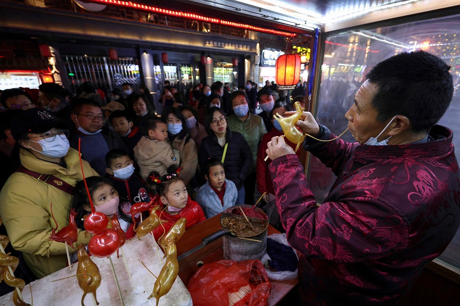 A man blows candy into various animal shapes in front of customers during the Lantern Festival, which marks the end of the Lunar New Year celebrations in Taiyuan, Shanxi province, China, on 26 February 2021. (STR/AFP)