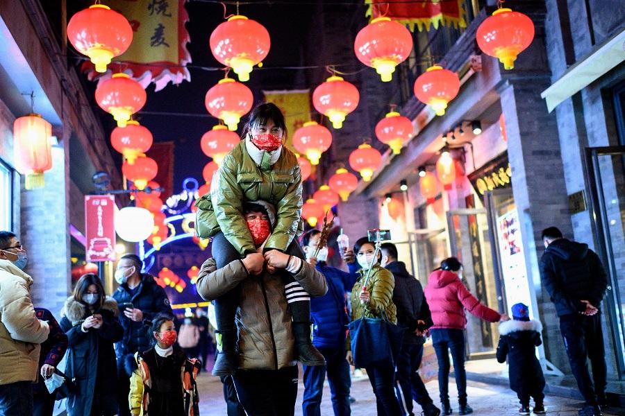 People wearing face masks walk at Qianmen street in Beijing, China, on 11 February 2021. (Noel Celis/AFP)