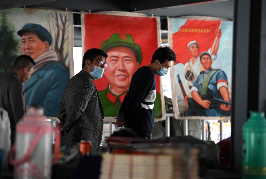People walk past pictures depicting the late Chinese Communist leader Mao Zedong at a stall in the Panjiayuan antique market in Beijing, China on 25 April 2021. (Noel Celis/AFP)