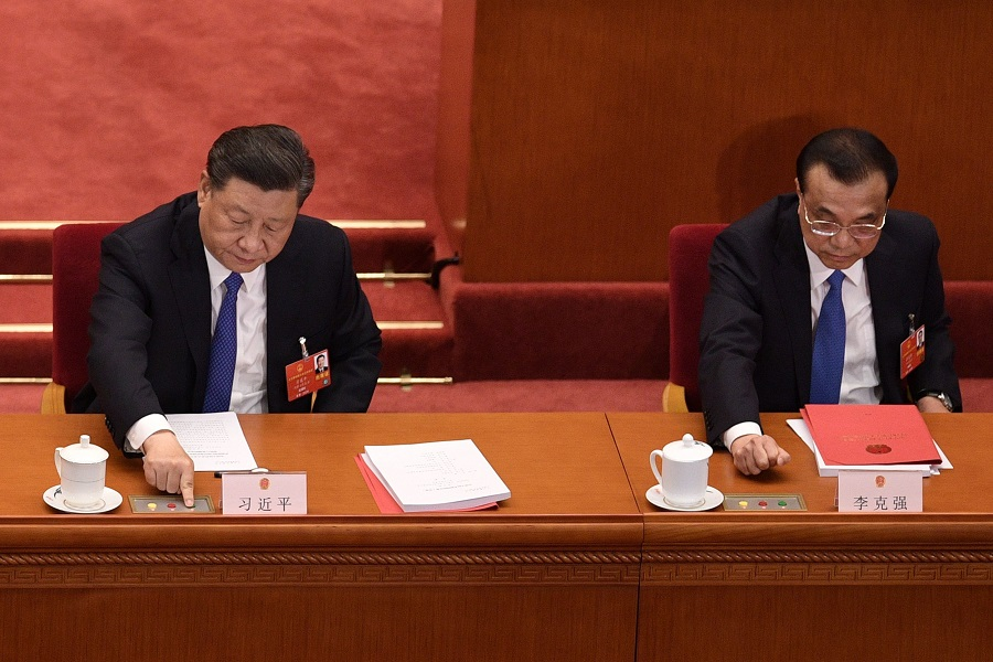 Chinese President Xi Jinping (left) and Premier Li Keqiang vote on a proposal to draft a security law on Hong Kong during the closing session of the National People's Congress at the Great Hall of the People in Beijing on 28 May 2020. (Nicolas Asfouri/AFP)