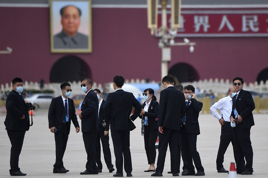 Security personnel are seen outside the Great Hall of the People for the second plenary session of the National People's Congress as a portrait of late communist leader Mao Zedong (back, left) is seen in the distance at Tiananmen Square in Beijing on 25 May 2020. (Noel Celis/AFP)