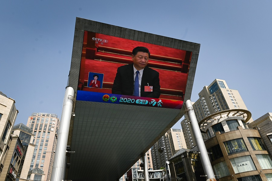 A outdoor screen shows live coverage of Chinese President Xi Jinping attending the closing session of the National People's Congress (NPC) in Beijing on 28 May 2020. (Wang Zhao/AFP)