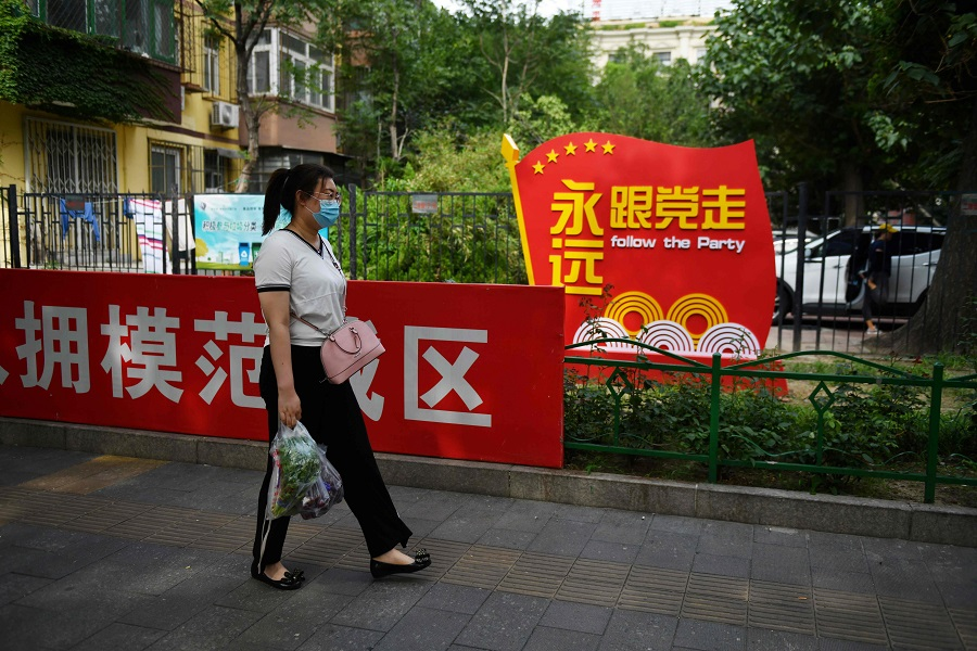 """A woman walks past a Communist Party slogan urging people to """"Follow the Party forever"""" outside a residential compound in Beijing on 6 July 2020. (Greg Baker/AFP)"""