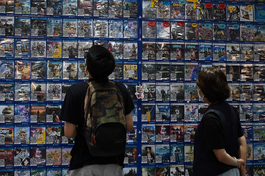 Customers browse computer games at a store in Beijing, China, on 10 September 2021. (Greg Baker/AFP)