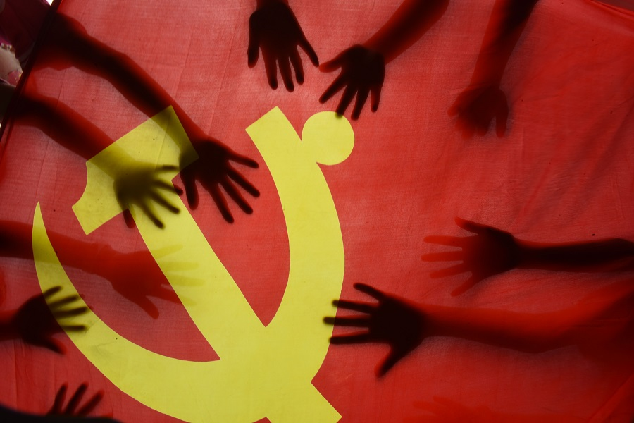 School children place their hands on the Communist Party flag during a class about the history of the Communist Party at a school in Lianyungang, Jiangsu, China, on 28 June 2020. (STR/AFP)