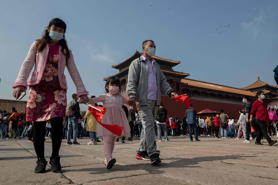 A family wearing face masks walks outside the Forbidden City (back) on 1 October 2020. (Nicolas Asfouri/AFP)