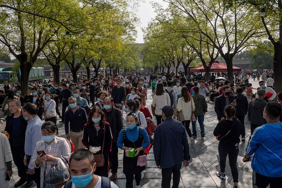 """People wearing face masks as a preventive measure against the Covid-19 coronavirus walk outside the Forbidden City (not pictured) during the country's national """"Golden Week"""" holiday in Beijing on 1 October 2020. (Nicolas Asfouri/AFP)"""