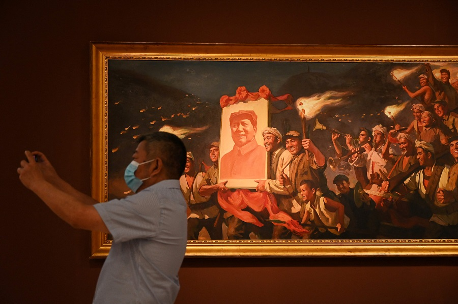 """A man takes a photo in front of a painting of people carrying a poster of late communist leader Mao Zedong titled """"Yan'an Torch"""", by artist Cai Liang, at an exhibition of art celebrating the 100th anniversary of the founding of the Communist Party in Beijing, China, on 24 June 2021. (Greg Baker/AFP)"""