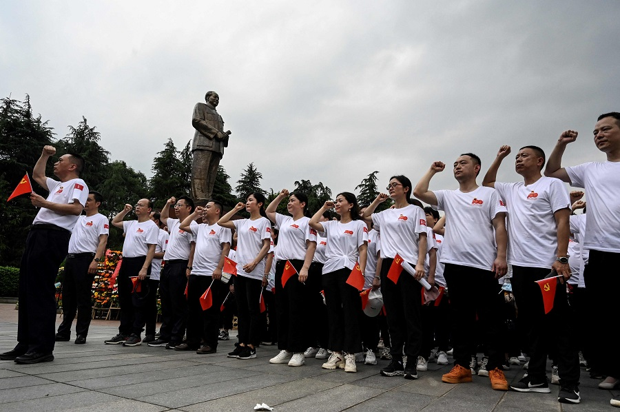 This photo taken on 26 May 2021 shows party members taking an oath next to a bronze statue of late Chinese communist leader Mao Zedong in Shaoshan, Hunan province, China. (Jade Gao/AFP)