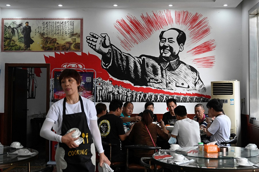This photo taken on 26 May 2021 shows people eating in front of an image of late Chinese communist leader Mao Zedong at a restaurant in Shaoshan, Hunan province, China. (Jade Gao/AFP)
