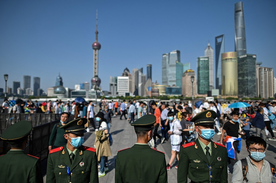 In this picture taken on 1 May 2021, Chinese paramilitary police keep watch as people visit the promenade on the Bund along the Huangpu River during the Labour Day holiday in Shanghai, China. (Hector Retamal/AFP)