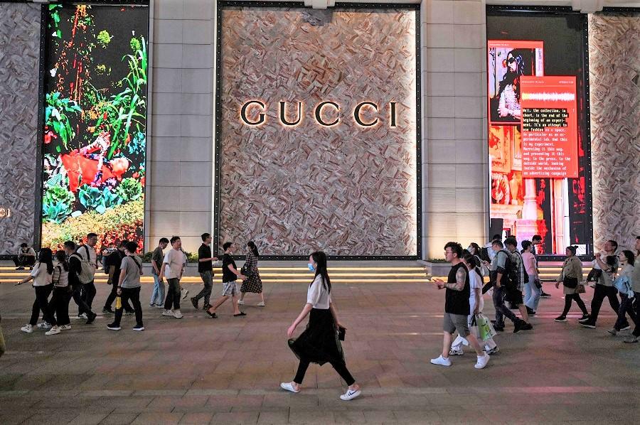 This photo taken on 25 May 2021 shows people walking past a designer shop in Shanghai, China. (Hector Retamal/AFP)