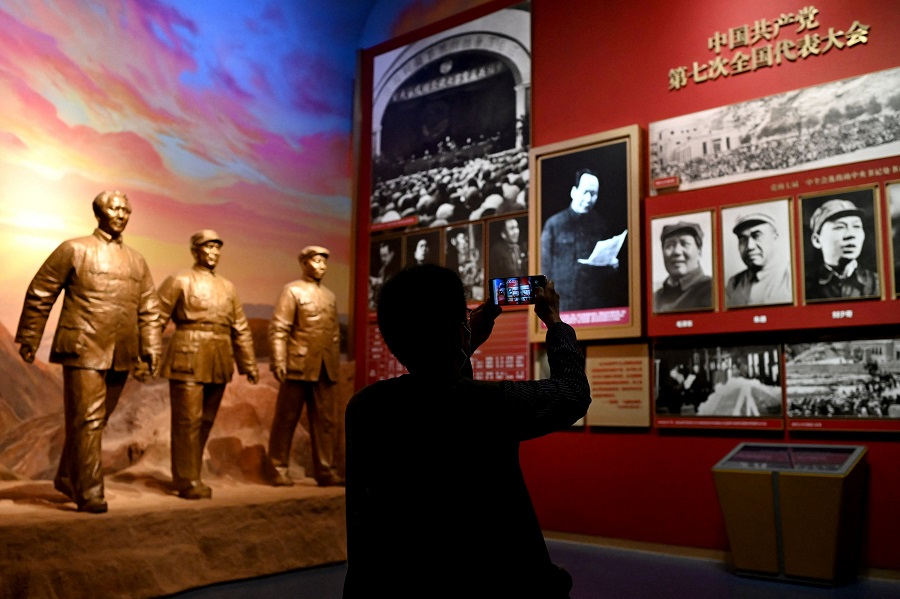 A journalist takes a photo of pictures depicting late Communist leader Mao Zedong, during a visit to the Museum of the Communist Party of China, near the Bird's Nest national stadium in Beijing, China, on 25 June 2021. (Noel Celis/AFP)