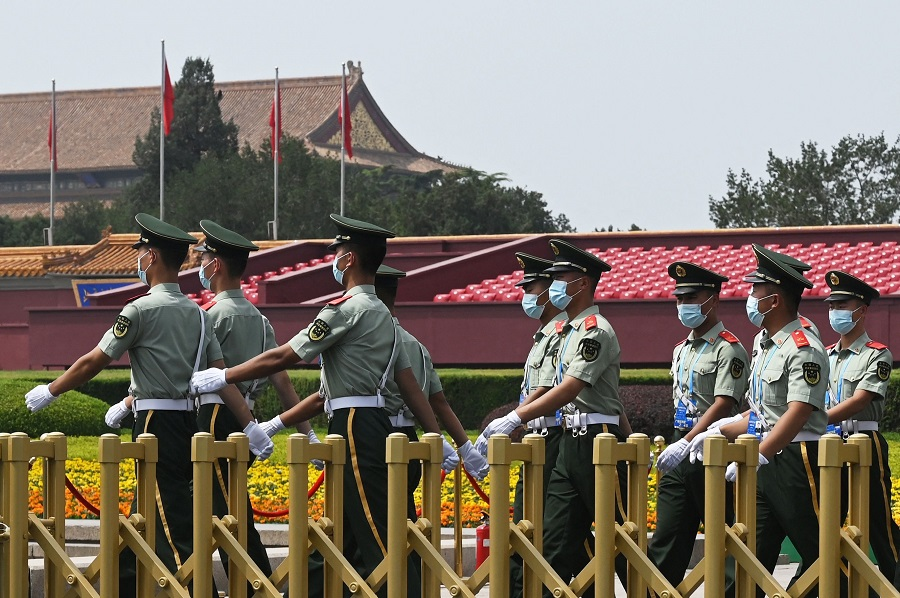 Paramilitary police officers patrol Tiananmen Square a day before an event marking the 100th anniversary of the founding of the Communist Party of China, in Beijing, China, on 30 June 2021. (Greg Baker/AFP)