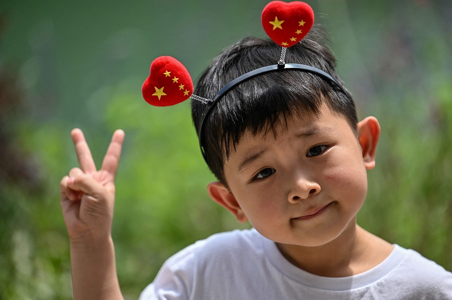A young boy wearing a head band poses in front of the First National Congress of the Chinese Communist Party in Shanghai, China on 1 July 2021, as the country marks the 100th anniversary of the founding of the party. (Hector Retamal/AFP)
