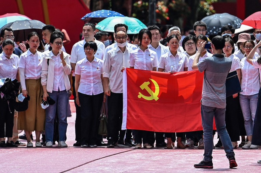 People pose for a picture with a flag of the Communist Party of China next to the First National Congress of the Chinese Communist Party in Shanghai, China, on 1 July 2021, as the country marks the 100th anniversary of the founding of the party. (Hector Retamal/AFP)