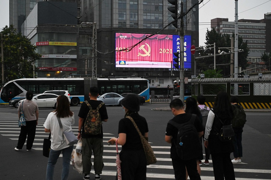 People wait to cross a road in Beijing, China, on 29 June 2021. (Greg Baker/AFP)