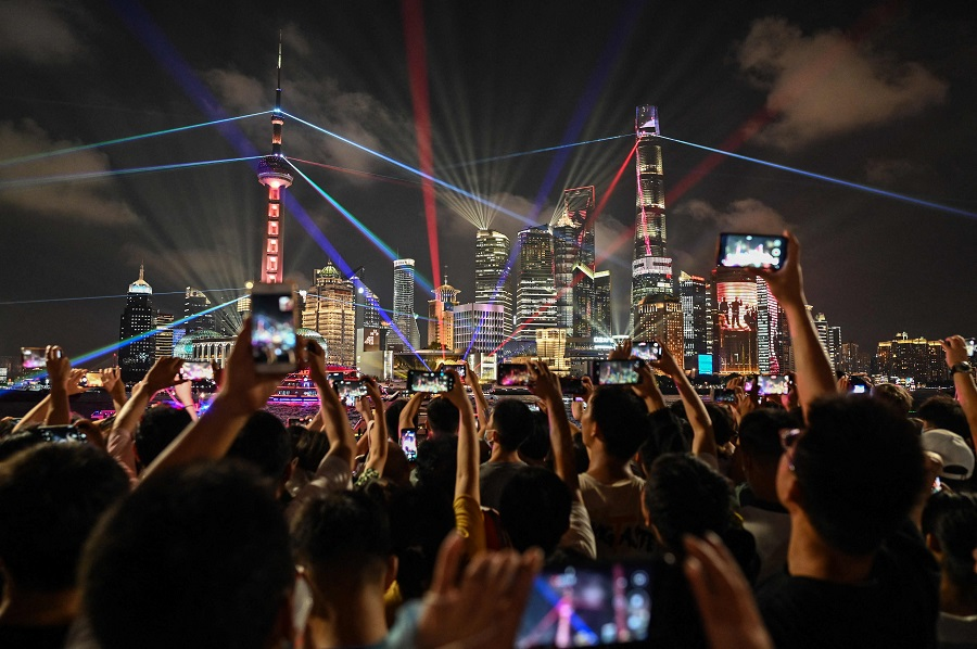 People take pictures as they look at a light show on the Bund promenade in Shanghai, China, on 30 June 2021, on the eve of the 100th anniversary of the Chinese Communist Party. (Hector Retamal/AFP)